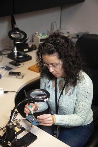 A woman uses a soldering iron to attach wires to a circuit board.