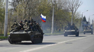 A group of military tanks driving down a street Description automatically generated with low confidence