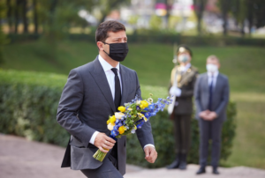 A person in a mask holding flowers Description automatically generated with medium confidence